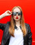 Fashion portrait pretty blonde woman with red lipstick wearing a rock black style and sunglasses having fun