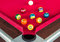 Many snooker balls or pool balls near the corner hole on red table
