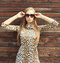Portrait beautiful blonde woman wearing a leopard dress and sunglasses