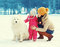 Happy family in winter day, mother and child walking with white Samoyed dog