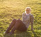 Adult, nice woman sitting on grass meadow