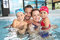 Portrait of happy family enjoying in swimming pool