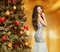 Christmas. Beautiful woman model in fashion dress. Makeup. Healthy long hair style. Elegant lady in red gown over xmas tree lights