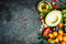 Fresh ingredients for salad or dip making: avocado, tomatoes,nuts,oil on rustic background, top view, place for text