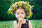 Beautiful happy little baby girl in a wreath on a meadow on the nature