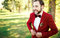Stylish groom in tuxedo laughs suit marsala red, burgundy bow tie. Man buttoning his jacket outdoors. Professional