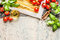 Pasta with fresh tomatoes, basil and olive oil on light shabby rustic background, top view, border.