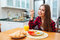 Cute smiling woman eating fried eggs for breakfast on kitchen