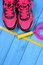Pair of pink sport shoes and accessories for fitness on blue boards, copy space for text