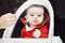 Portrait of cute adorable Caucasian little baby boy sitting in high chair in kitchen eating meal puree