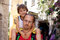 Young father, carrying his toddler boy on his neck, summertime,