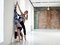 Instructor helps to do yoga exercise on an stretching on wall
