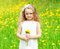 Beautiful little girl child on meadow with yellow dandelion flowers in sunny summer