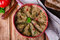Babaganoush with tomatoes, cucumber and parsley - arabian eggplant dish or salad on wooden background. Selective focus