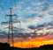 Silhouettes high voltage electric pylon in sunset background