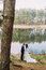 Romantic groom and his charming new wife kissing on the shore of forest lake