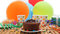 Chocolate birthday cake with a blue candle burning on rustic wooden table with background of colorful balloons, gifts