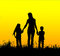 Silhouette mother and child holding hands at sunset