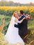 Groom softly kiss bright happy redhair bride with unusual appearance in the sunny sunflower field