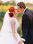 Bright happy redhair bride with unusual appearance and handsome groom softly kissing in sunny sunflower field