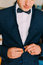 Close-up shot of young caucasian man wearing stylish elegant suit with bow tie
