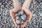 Inner balance concept: hands holding stones, land background. Earth day, eco friendly. Nature wallpaper. Symbol of