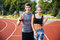 Young man and woman standing on athletics race track