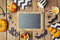 Halloween holiday background with chalkboard, pumpkin and candy.