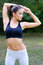 Beautiful muscular fitness girl exercising in summer nature