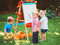 Group of three white Caucasian toddler children kids boys and girl standing outside in summer autumn park by drawing easel