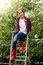 Teenage girl in red gumboots posing on ladder at apple garden