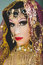 Headshot woman dressed in traditional hindu clothing, heavily decorated in gold and elegant veil, posing artistically