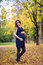 Portrait of happy lovely and beautiful caucasian young pregnant woman in autumn park