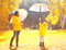 Moment of happiness! Happy family with umbrellas in sunny autumn rainy day, young mother and child in jacket outdoors