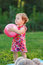 Little girl holding pink ball on lawn in park