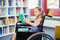 Disabled school girl reading book in library