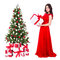 young beautiful woman in red dress with big gift box and decorated christmas tree isolated on white