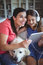 Happy mother and daughter sitting with pet dog and listening to music on headphones