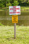No fishing or hunting and No feeding signs on wooden post in nat