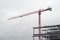 Red crane on cloudy sky with building structure construction site
