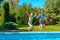 Children jump to swimming pool water and have fun, kids on family vacation