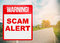 A warning sign warning about Scam in road.