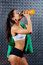 Attractive fitness woman with bottle and towel indoor portrait, drinking.