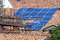Renewable clean green energy saving efficient photovoltaic solar panels on multiple gable suburban house roof over blue