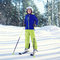 Professional skier child boy in sportswear and helmet, sunny winter snowy day at hill mountain over forest