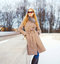 Fashion beautiful young blonde woman wearing coat jacket and sunglasses in winter city