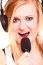 Woman singing to microphone wearing headphones