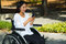 Young brunette woman sitting in wheelchair smiling with positive attitude, using mobile phone, outdoors environment