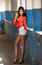 Beautiful girl with red shirt and white shorts posing in old hall with columns blue painted. Attractive long hair brunette