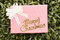 Pink Gift box on green lawn and gold text of Merry Christmas.